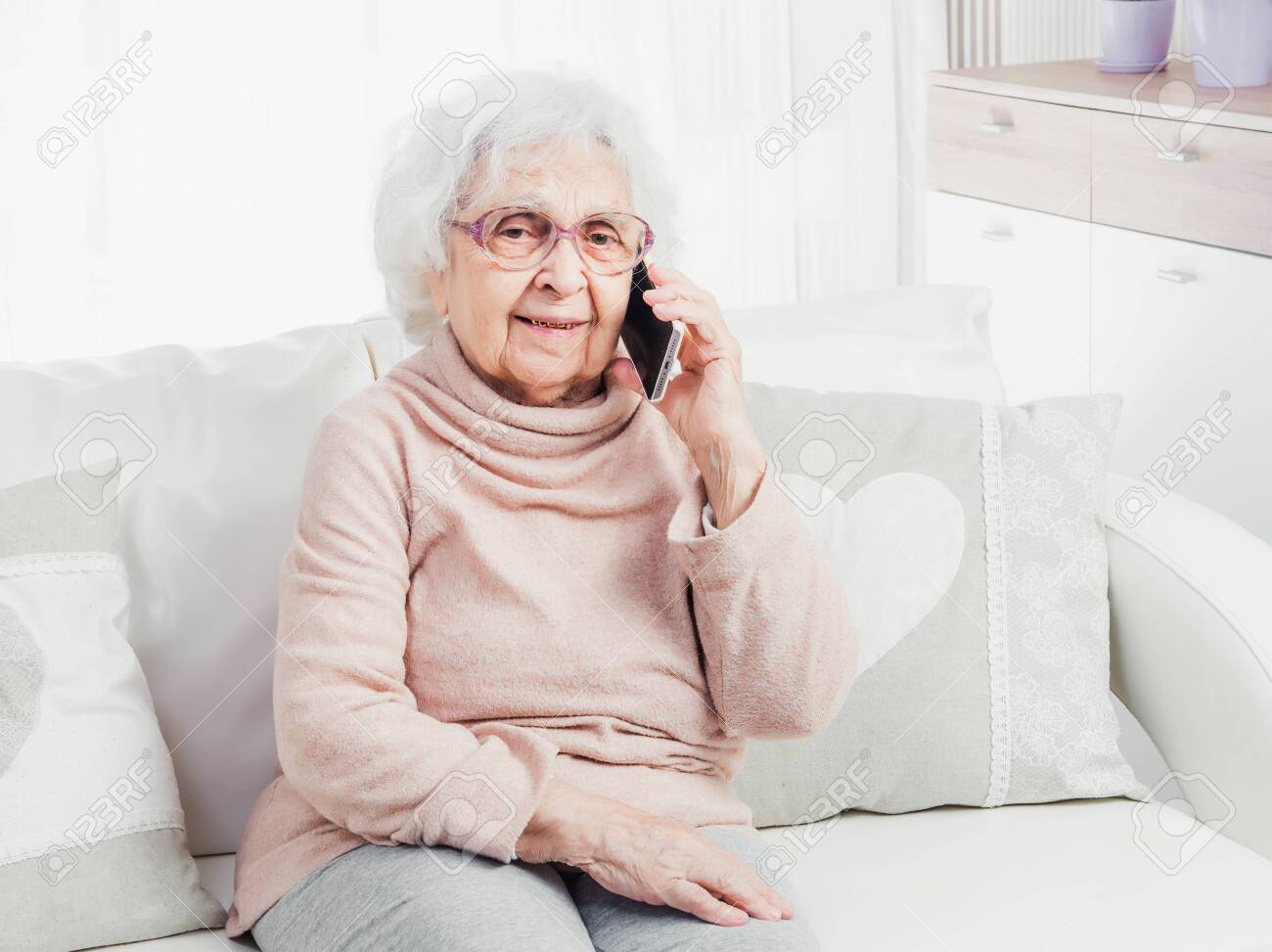 Great-grandmother talking by smartphone - 118405623