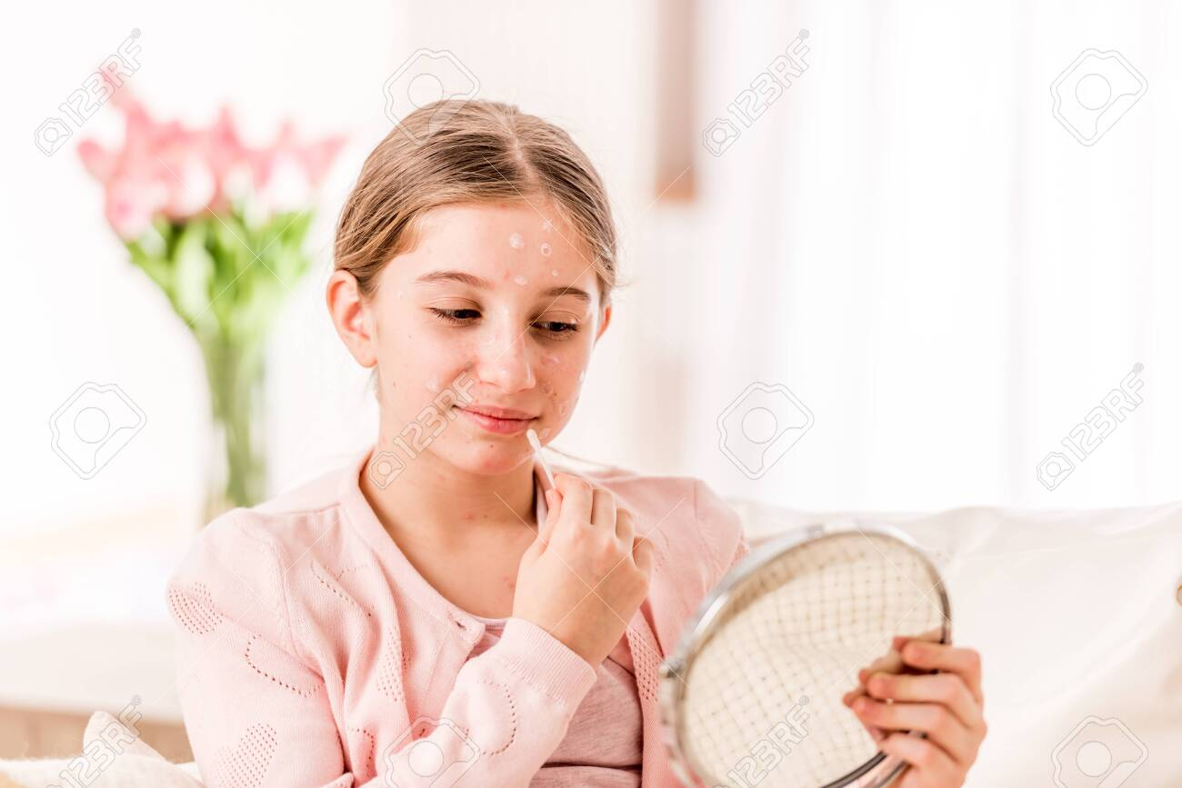 Ill girl trying to look good at the mirror - 126422650