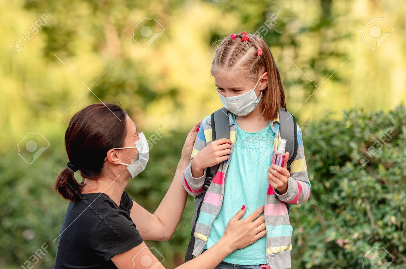 Mother putting mask on daughter before school - 152955784