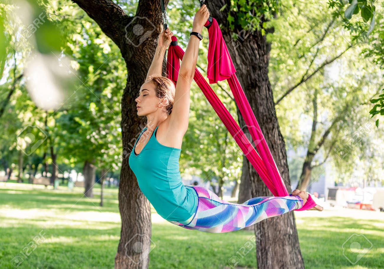 Girl doing fly yoga - 172489944