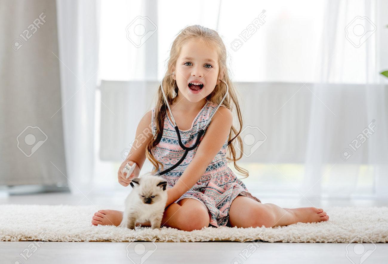 Girl with ragdoll kitten - 173455744