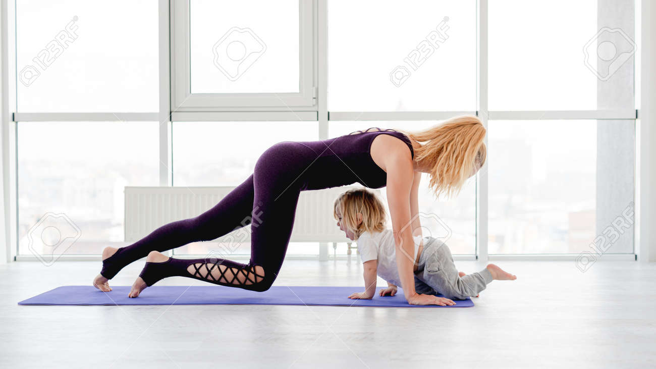 Mother and child practicing yoga - 173370706