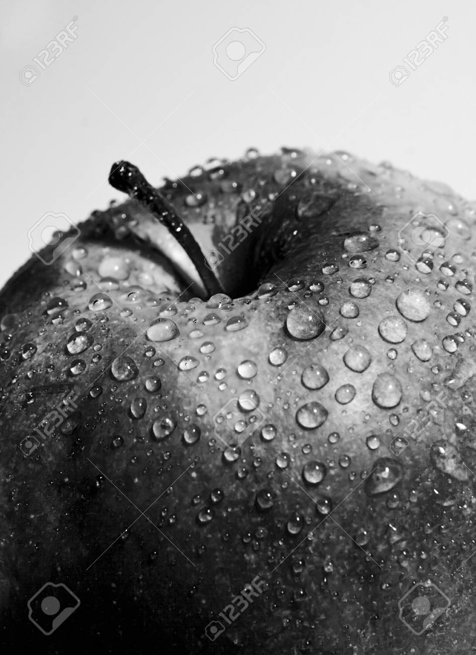 Juicy red apple with drops close up of black and white