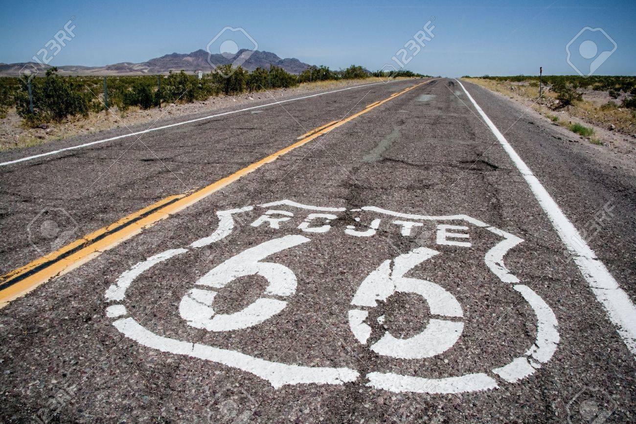 long road with a route 66 sign painted on it stock photo, picture