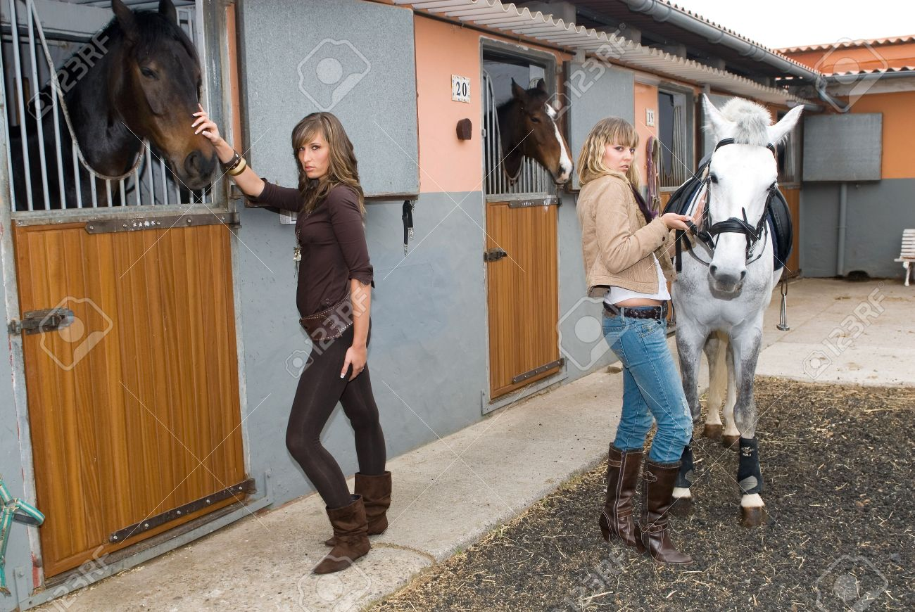 two hispanic girls with horses in the stable - 2802692