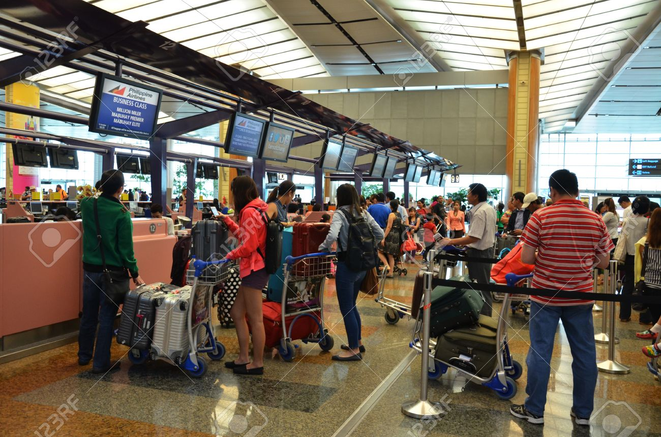 Tourists queue in fronts of ticket counter at Singapore airport - 22888500