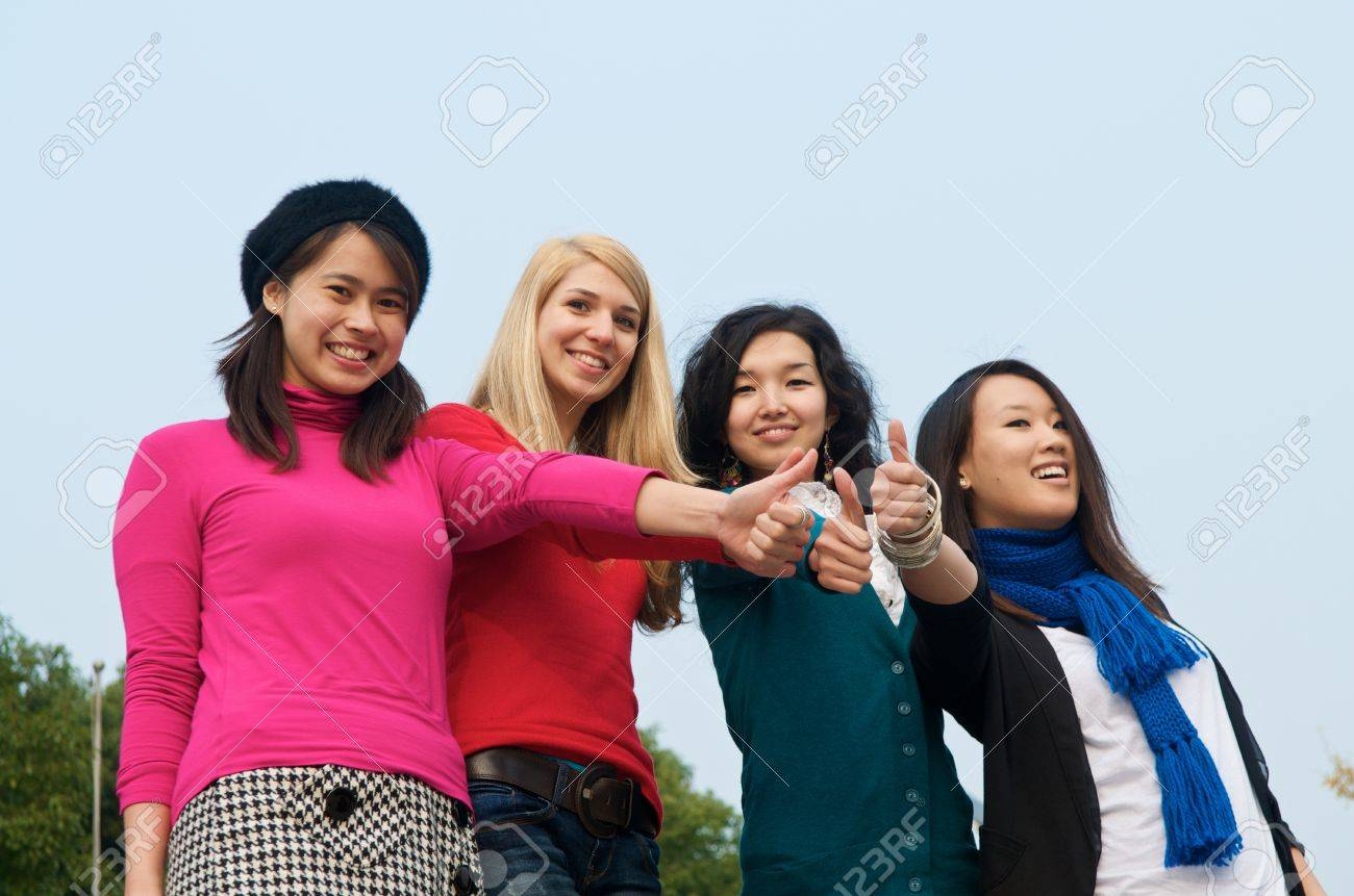 Group of 4 female students outdoor thumbs up Stock Photo - 14994781