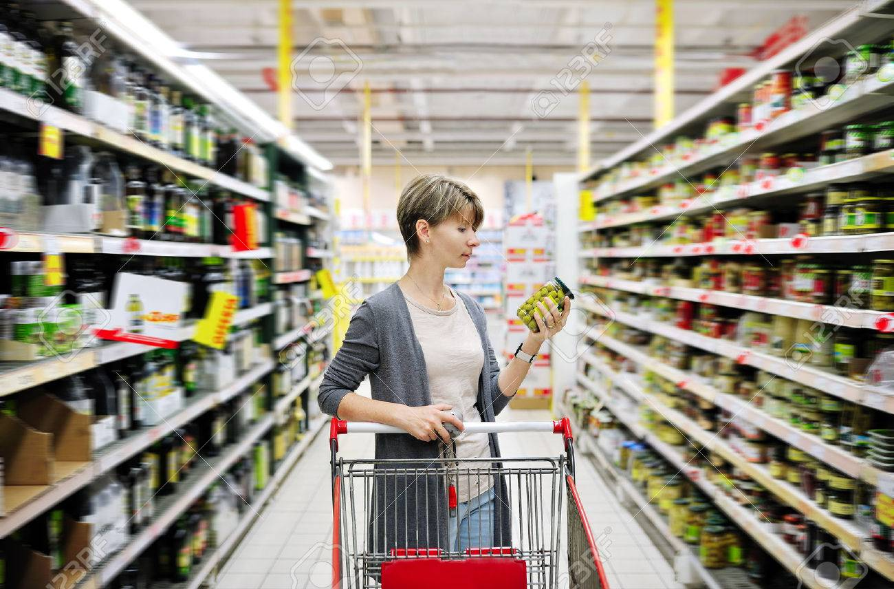 pretty woman with a cart shopping and choosing goods at the supermarket - 23387221