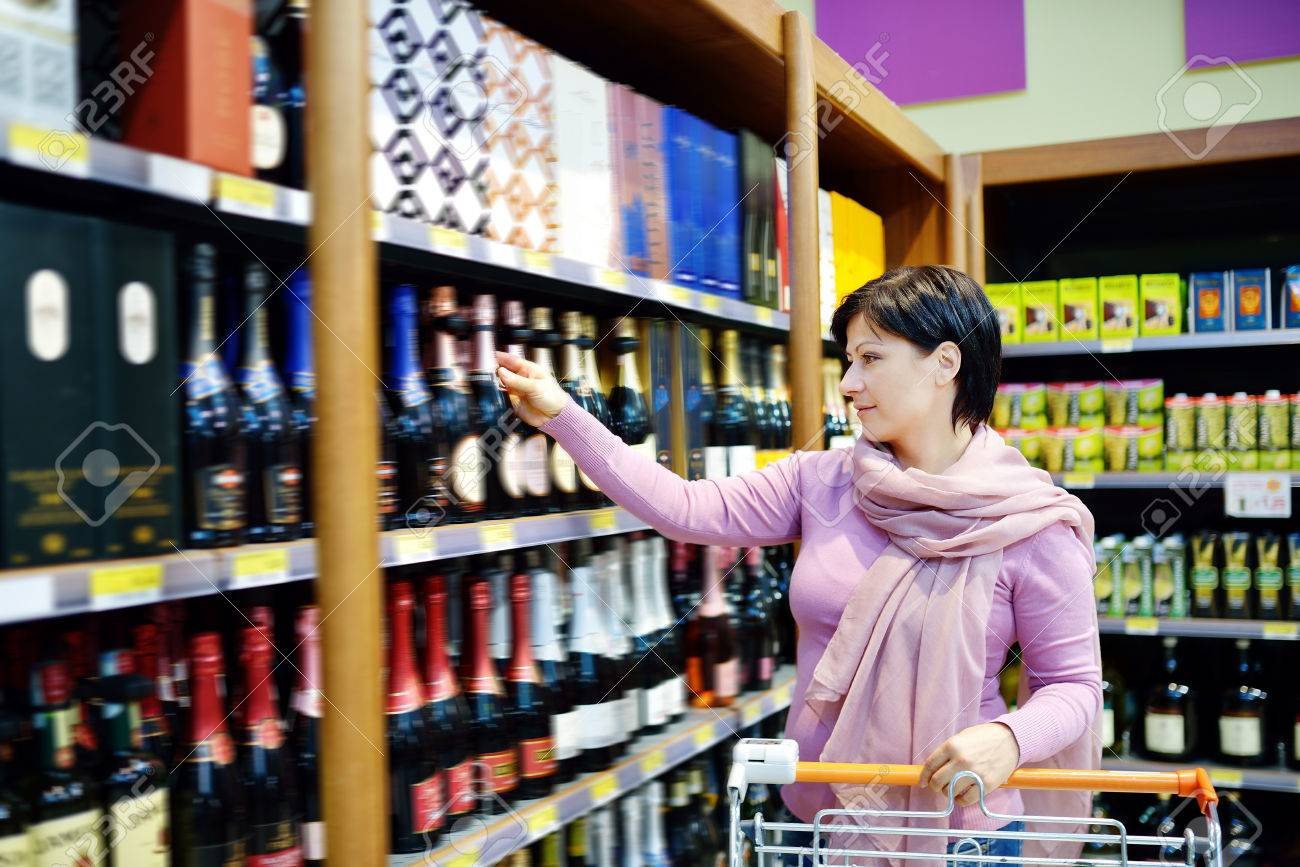 pretty caucasian woman shopping and choosing goods at supermarket - 24546759