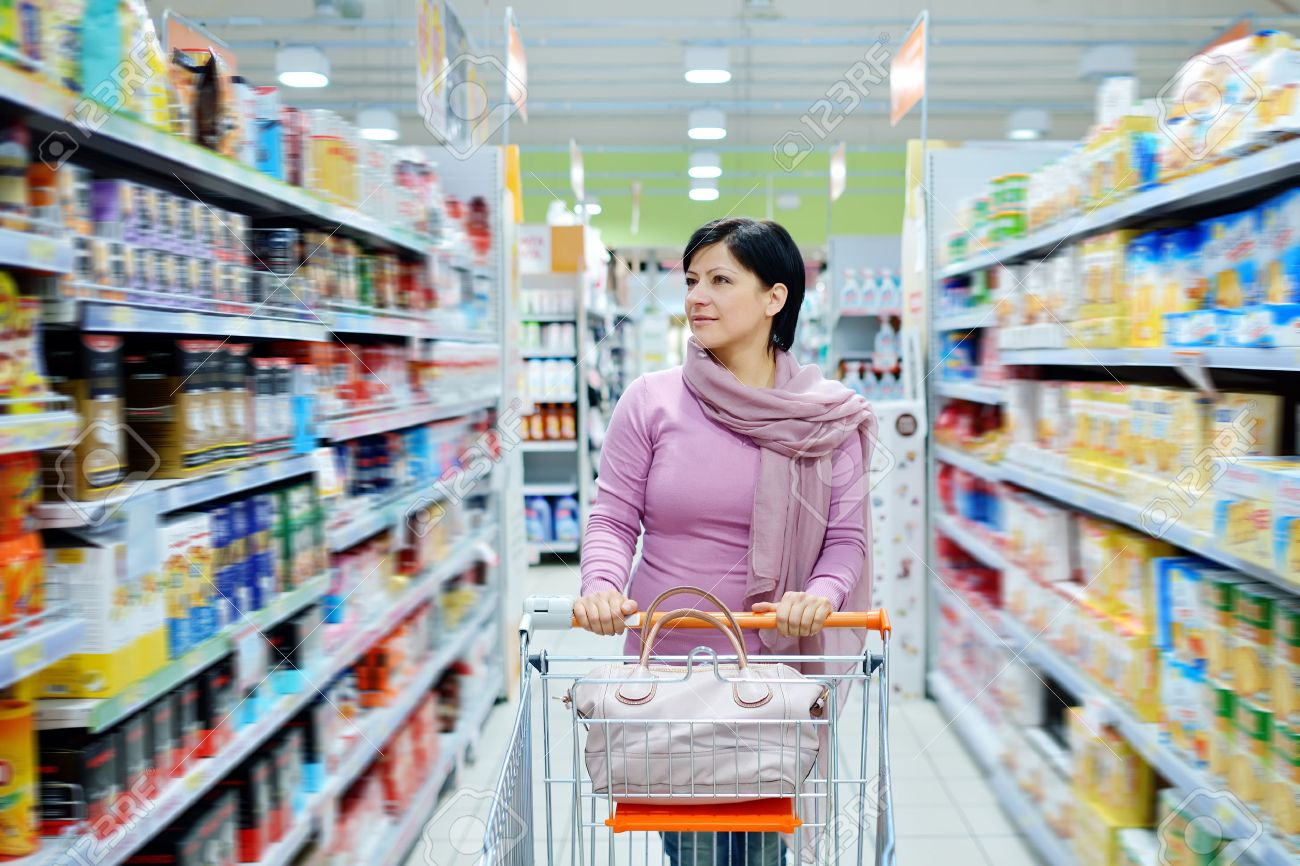 pretty smiling woman pushing shopping cart looking at goods in supermarket - 24984470
