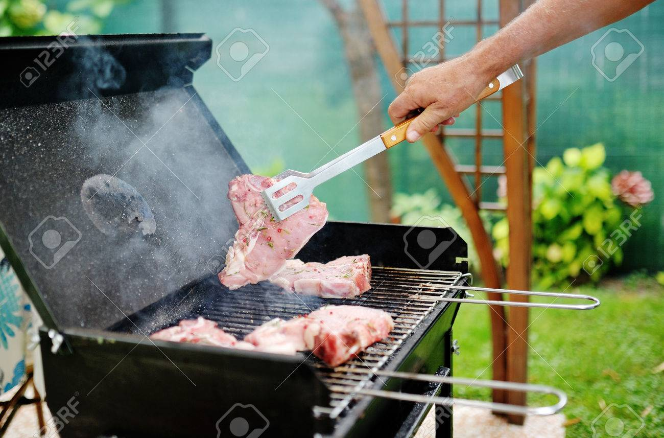 Man hand at a barbecue grill preparing meat for a garden party - 27573749