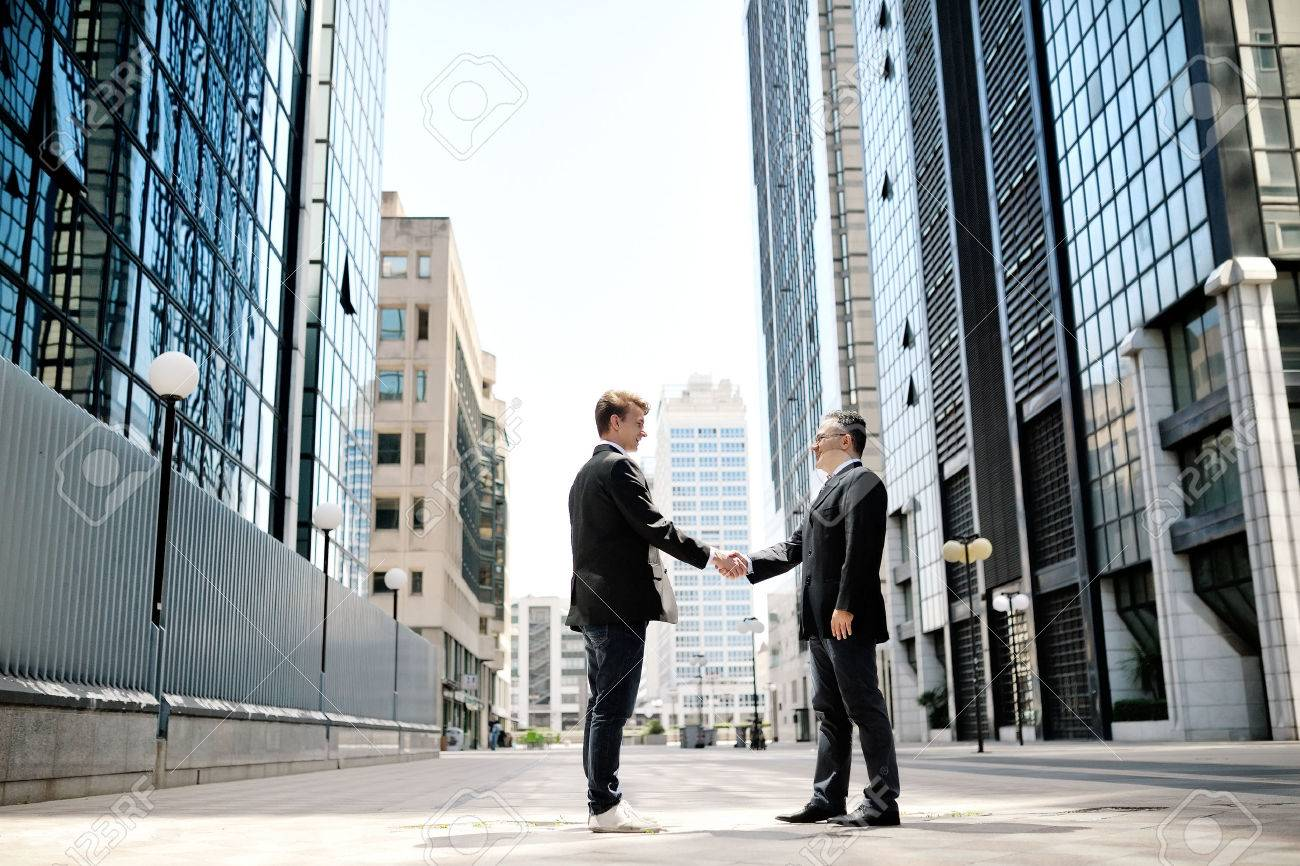 two businessmen shaking hands on background modern office corporate buildings - 29303187