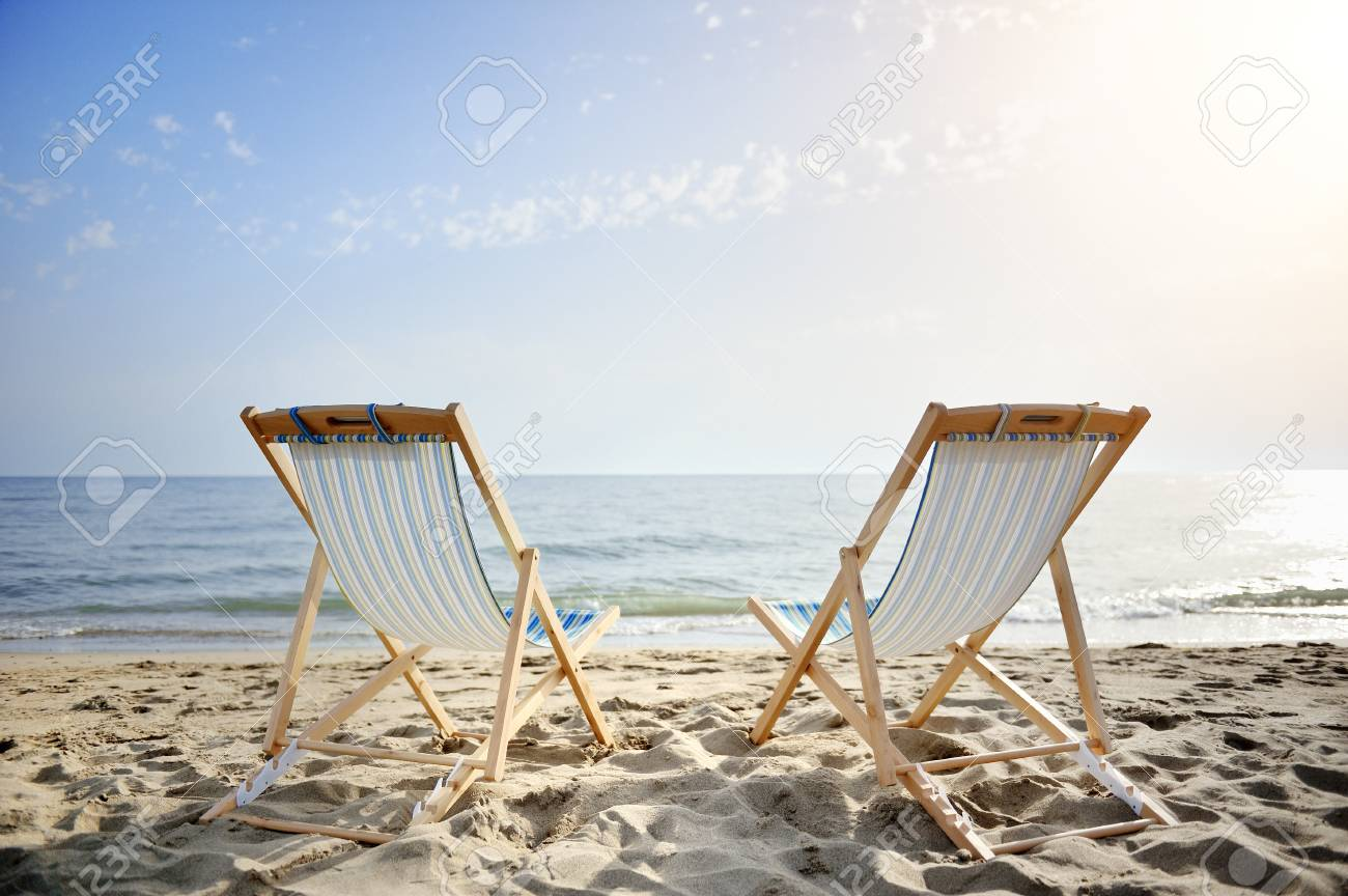 couple of chairs on sandy beach at sunset looking for the blue sea - relaxation concept - 29815272