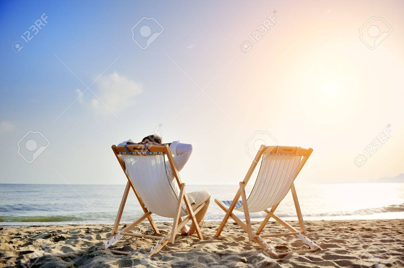 man on the beach relaxing on deck chair waiting for his girlfriend - 30534228