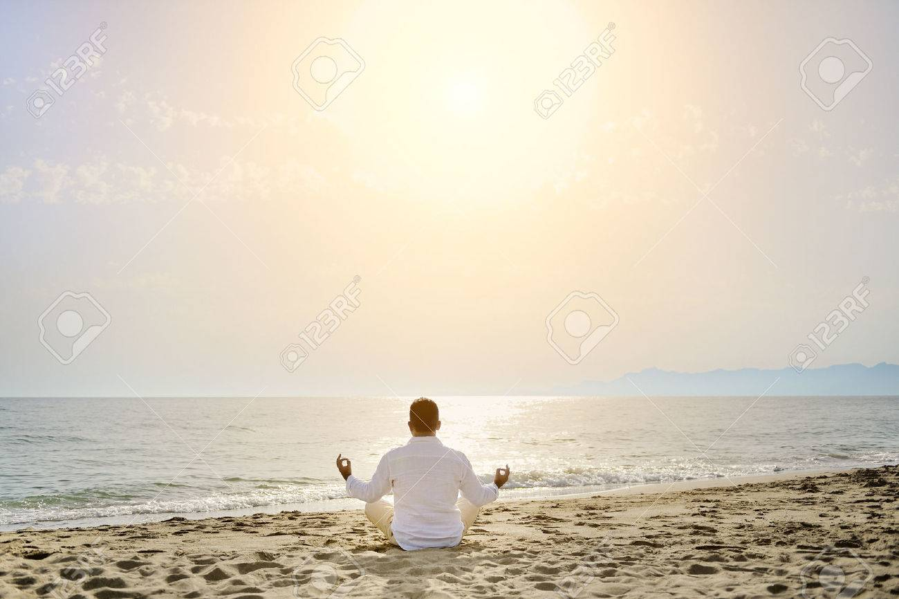 man doing yoga meditation exercises on the beach at sunset- healthy lifestyle concept - 30538562