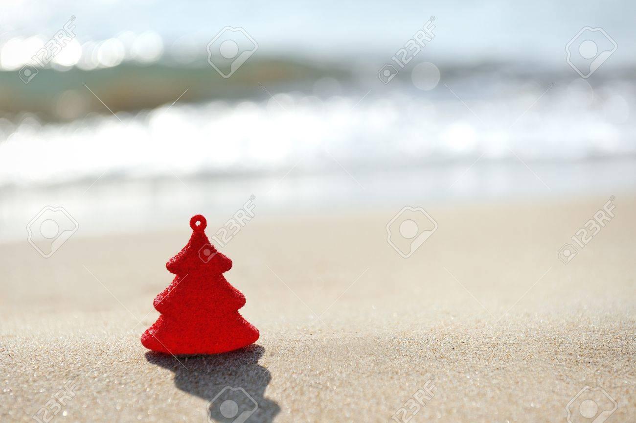 red christmas tree decoration on sand beach - 47544366