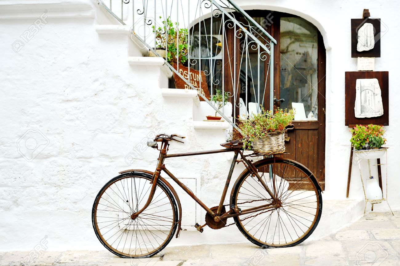 vintage rusty bicycle against a wall in white city Ostuni, Apulia, Italy. - artistic picture italian style concept - 58339358