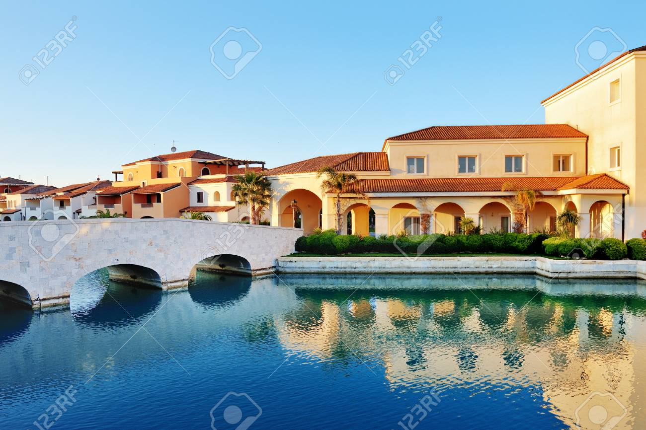 Policoro, Italy - scenic view of canal, bridge and houses - 77503078