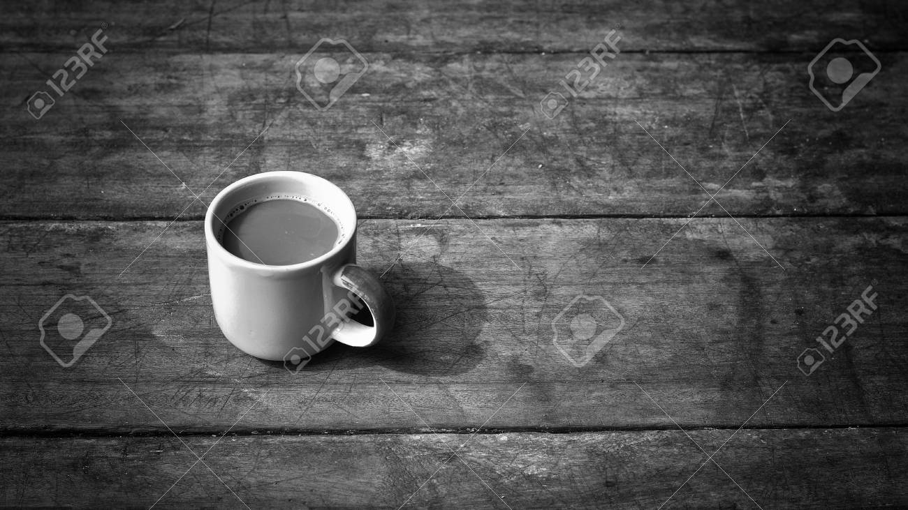 Hot coffee on old wooden plank in low key black and white style black and
