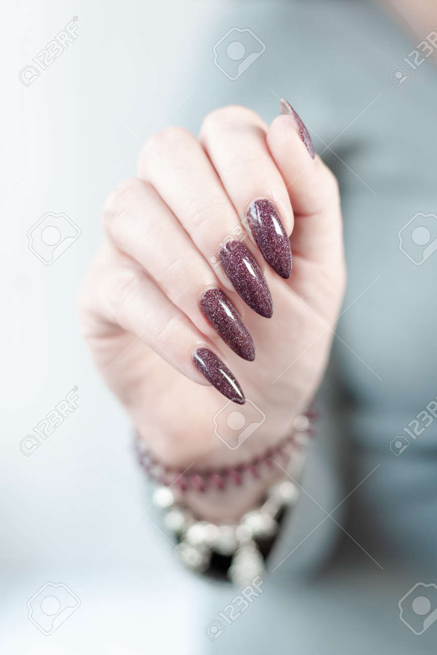 Woman hand with long nails and a bottle of dark brown red nail polish - 162540319