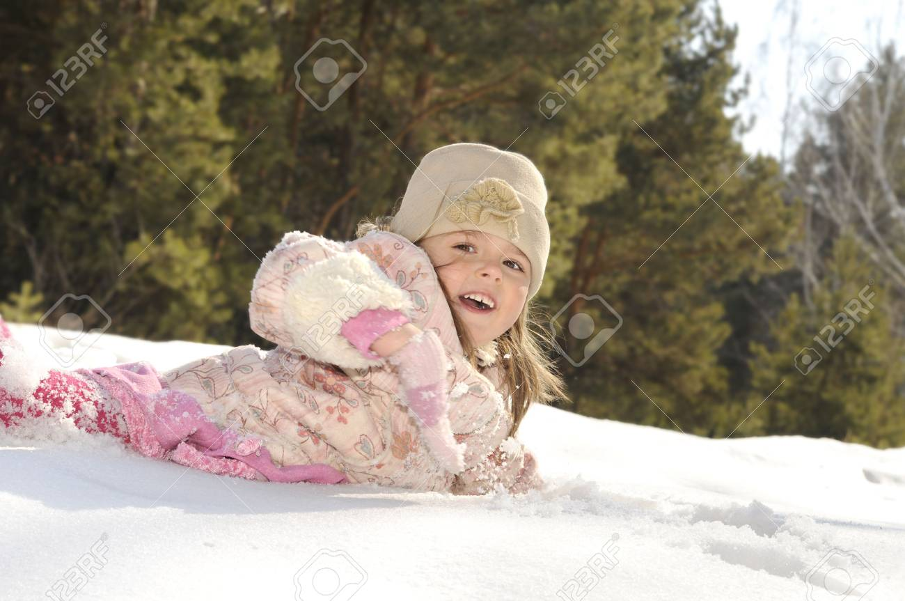 The little girl lays in a snow on the nature in the winter Stock Photo - 4563934