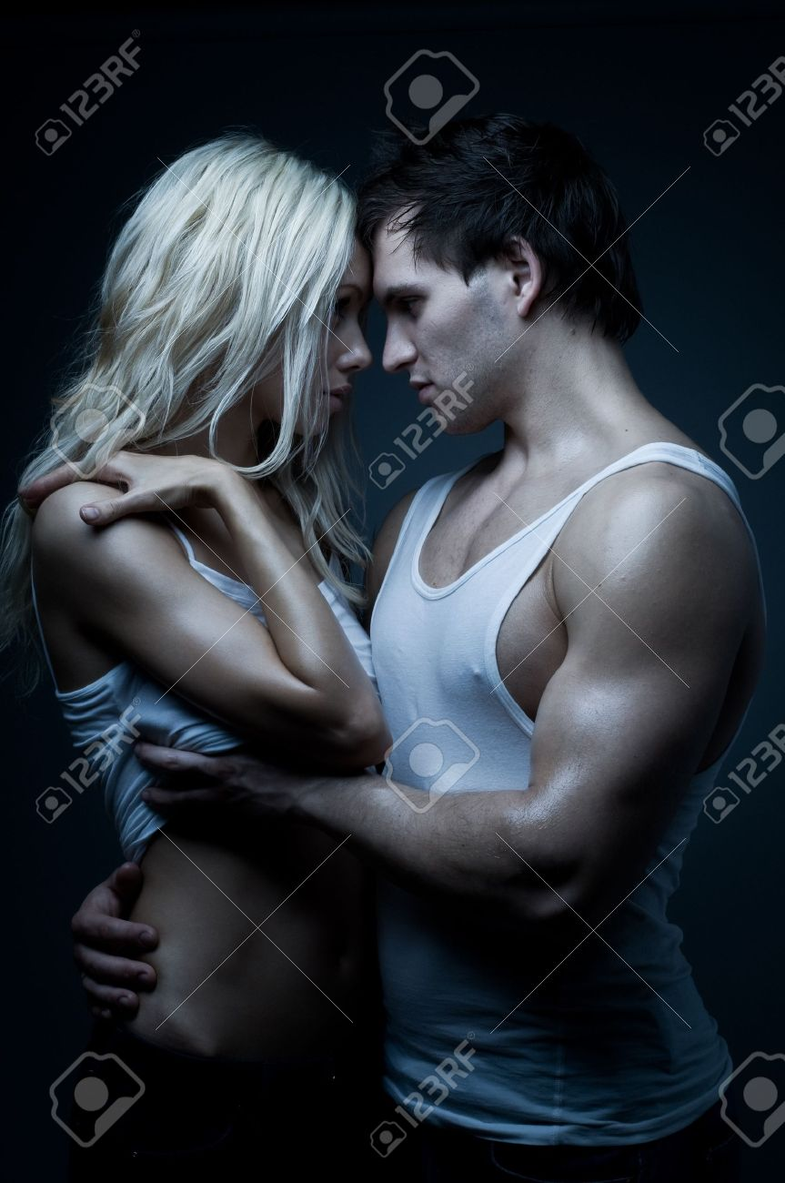 muscular handsome sexy guy with pretty woman, on dark background, glamour blue light Stock Photo - 8874211
