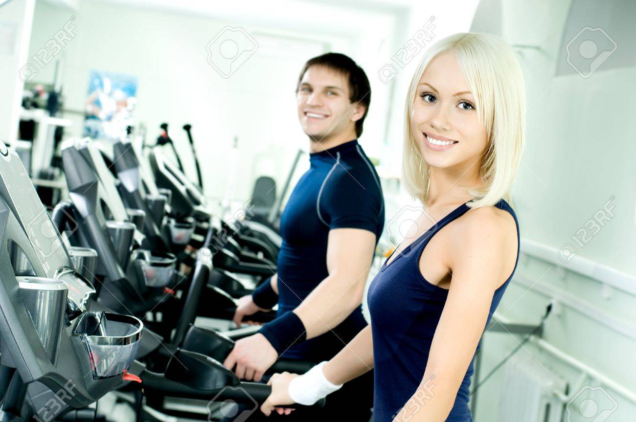 happy cutie athletic girl and guy,  execute exercise on  running track  and smile, in  sport-hall Stock Photo - 9209211