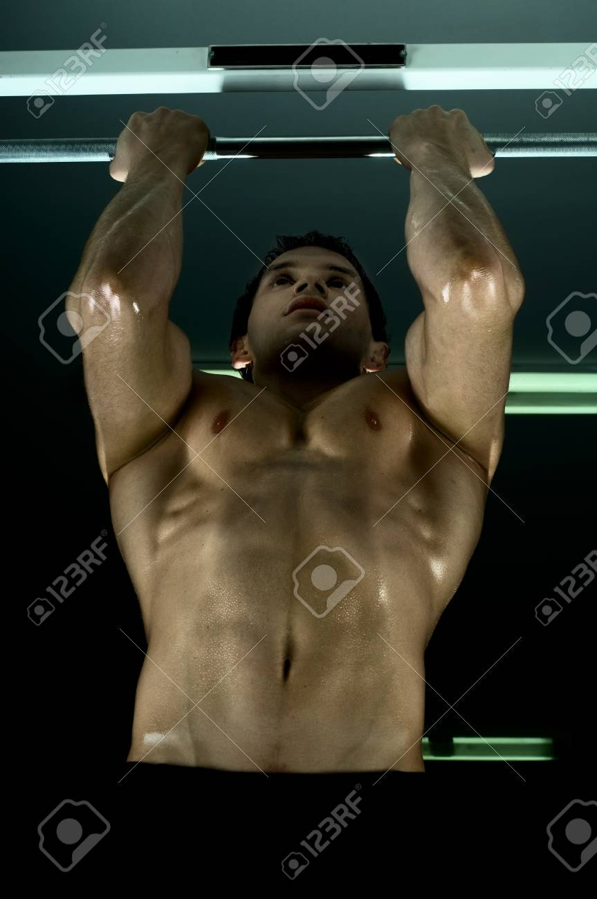 very power athletic guy ,  execute exercise tightening  on horizontal bar, in  sport-hall, glamour light Stock Photo - 9207864