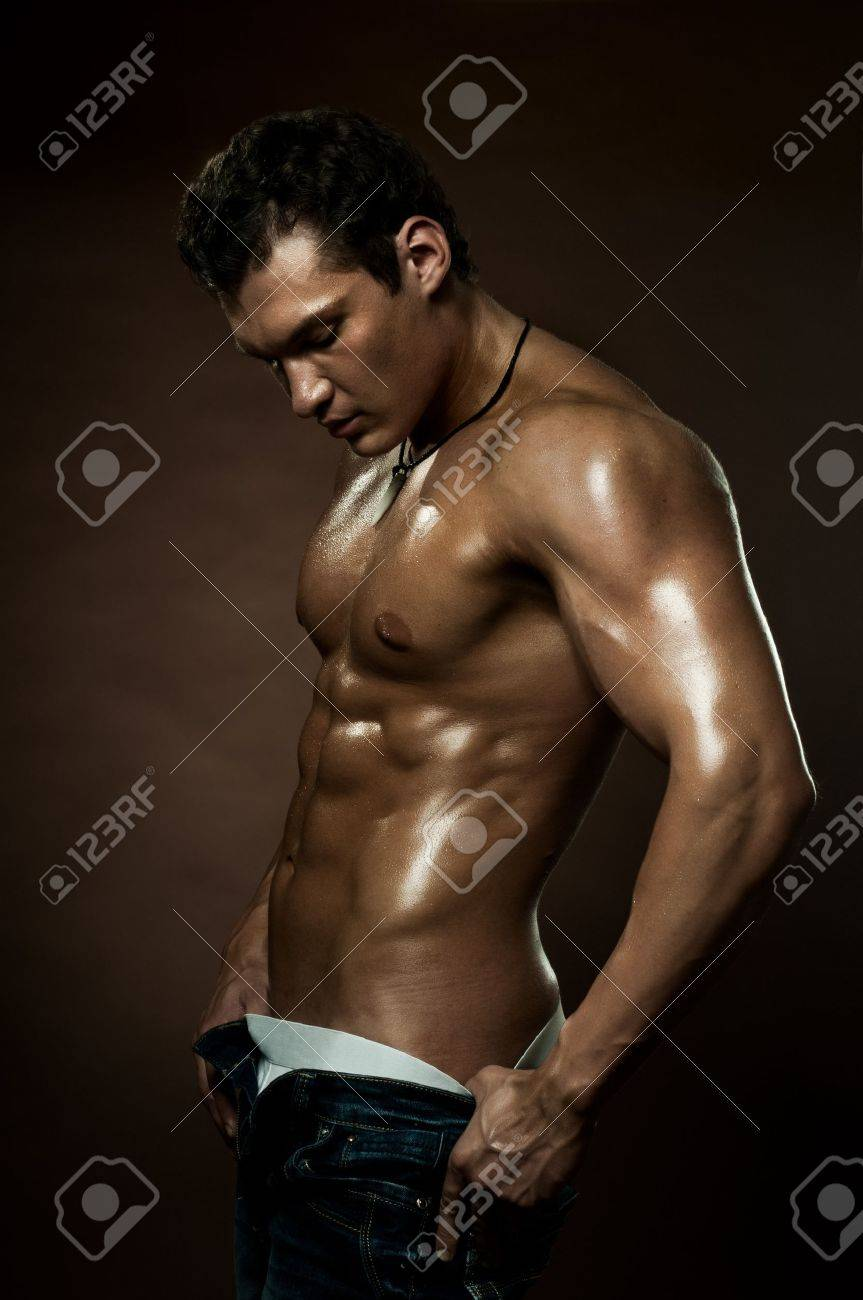 Stock Photo - the very muscular handsome sexy guy on dark brown background,  strict