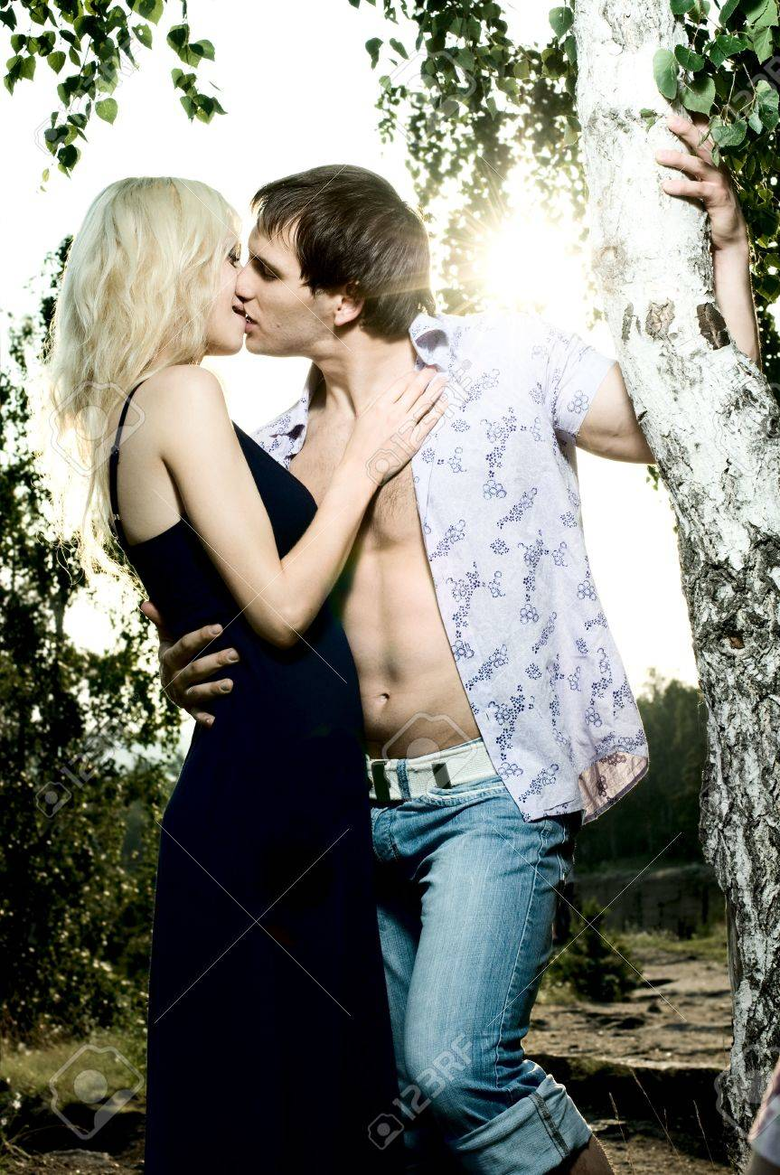 romantic evening date on nature, couple on beautiful sunset kiss Stock Photo - 11219940