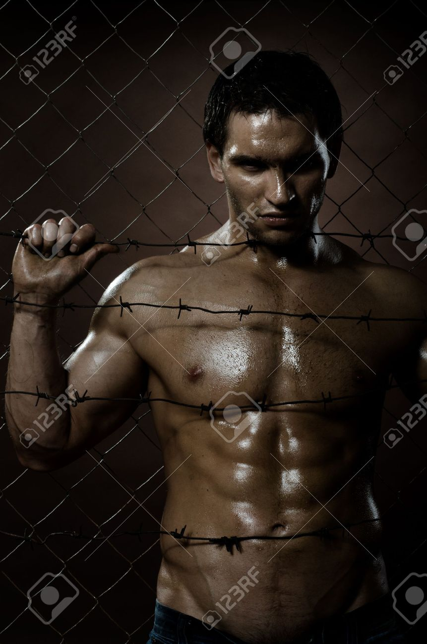 the very muscular handsome felon guy ,  out of netting   steel fence Stock Photo - 11386174