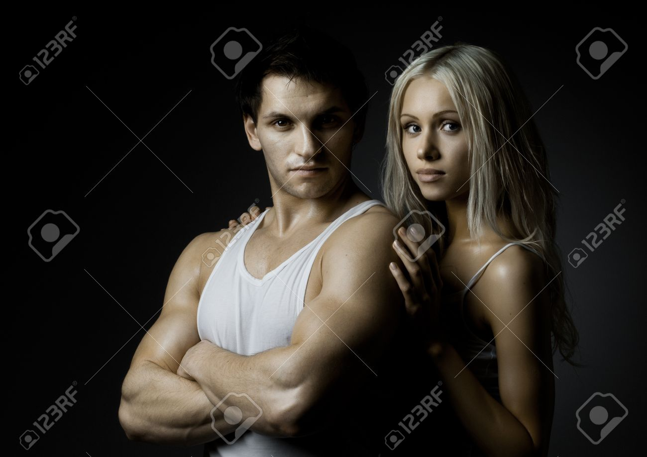 muscular handsome sexy guy with pretty woman on dark background, look on camera Stock Photo - 12071528