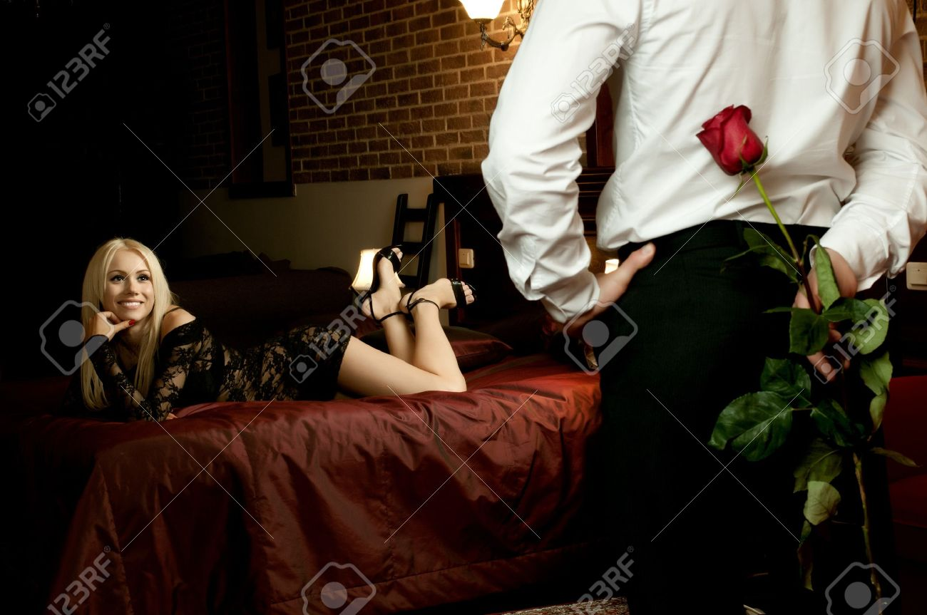 romantic evening date in hotel room, guy with red rose and sexy