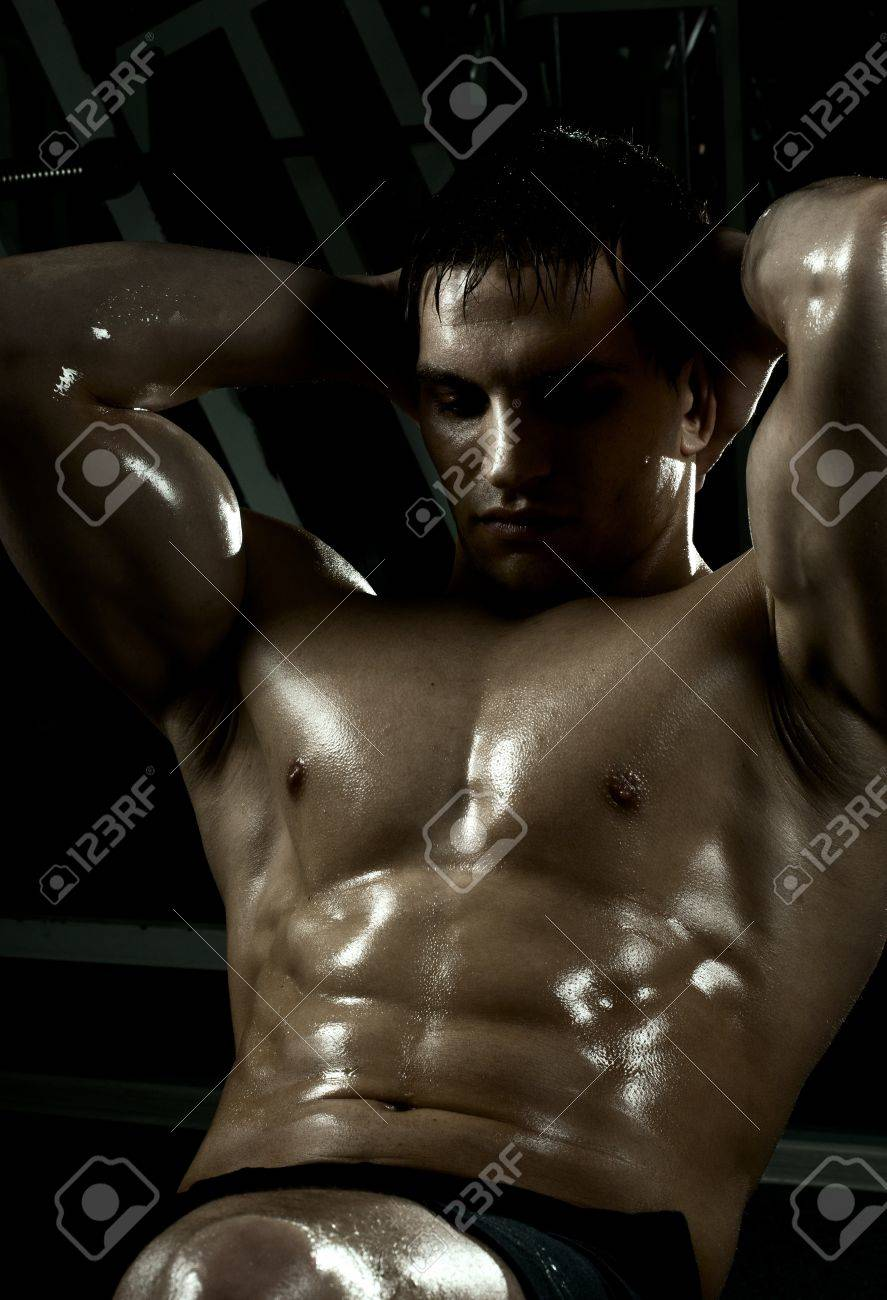very power athletic guy ,  execute exercise on muscles belly, in  dark sport-hall Stock Photo - 12228956