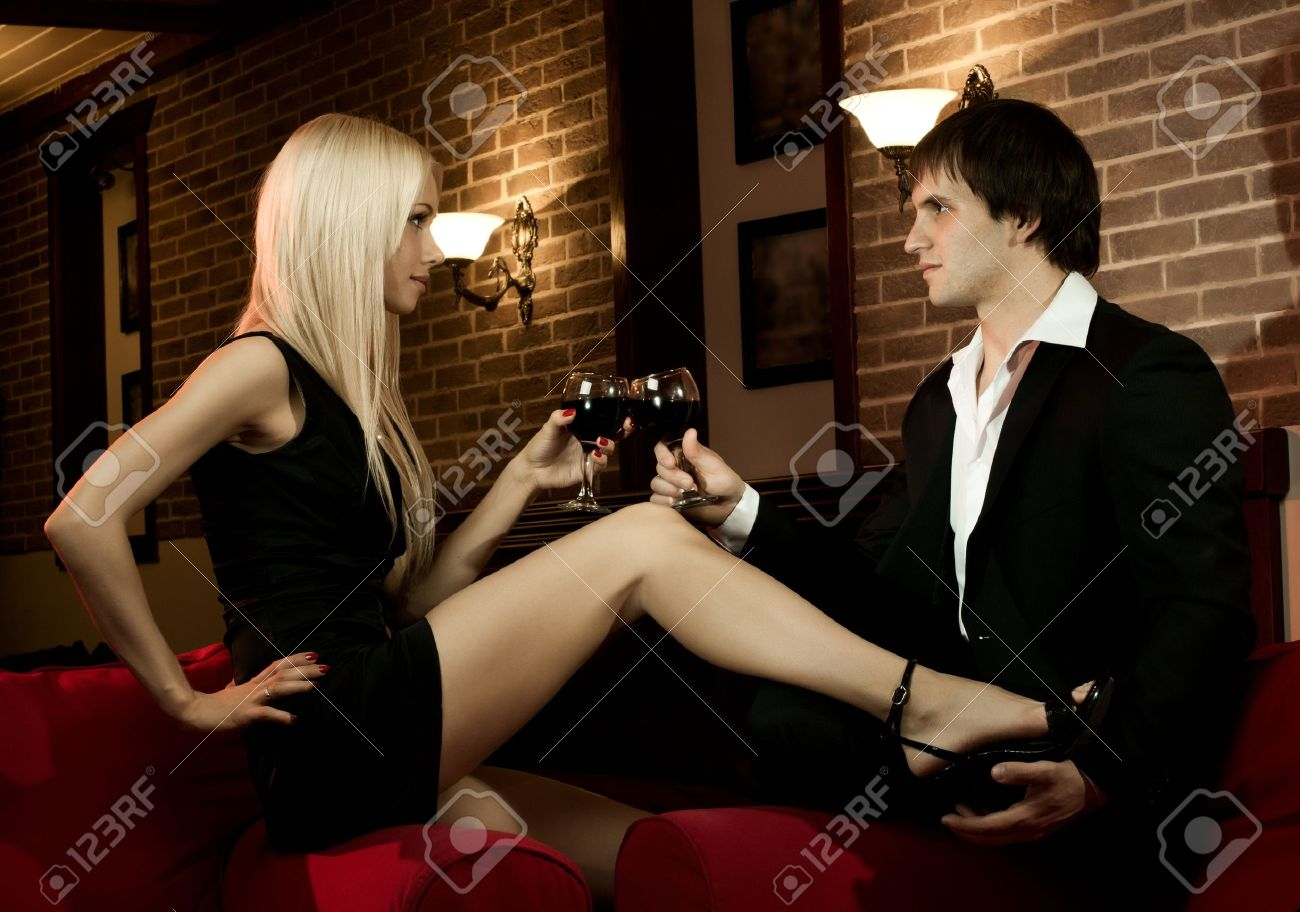 romantic evening date in hotel room,  happy couple with wine glass sit on red sofa Stock Photo - 12466079