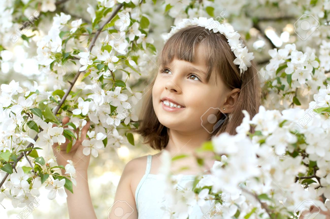 The beautiful little girl, with bush blossoming apple-tree, smiles Stock Photo - 12229132
