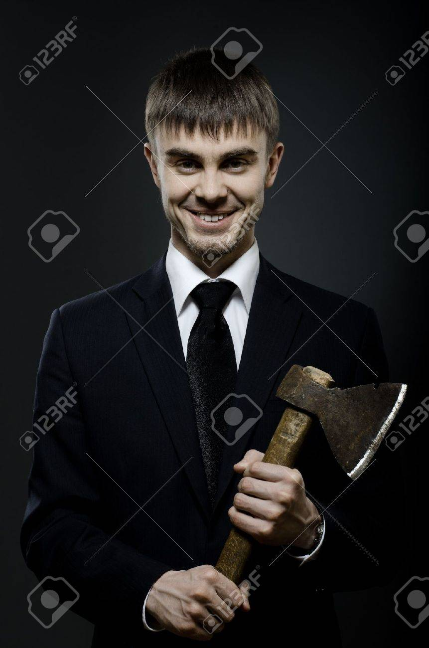 portrait  the  beautiful  businessman  in black costume and black necktie with axe, sinister look and smile Stock Photo - 12773926