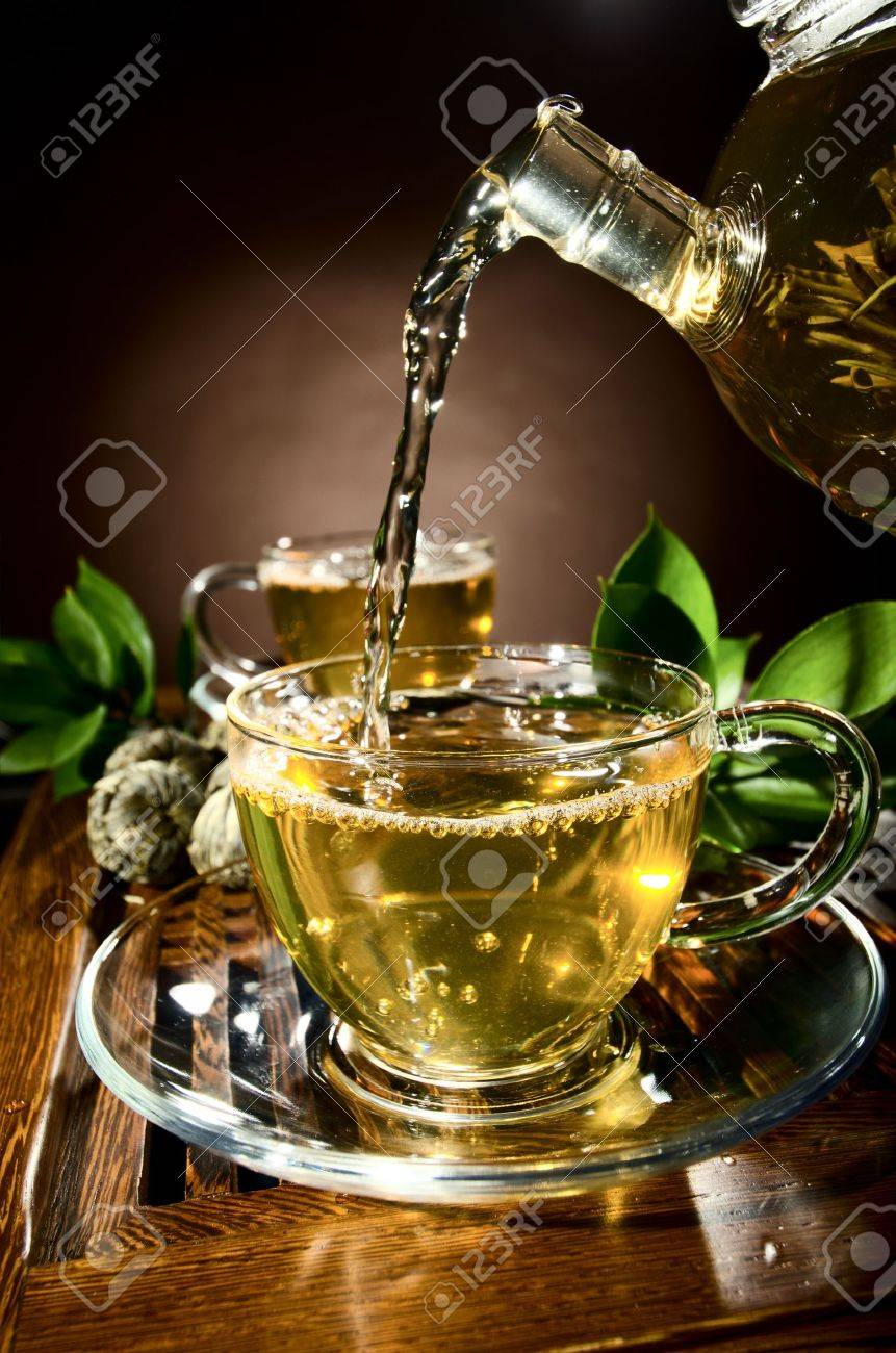 vertical photo, of the glass teapot flow green tea in cup on brown background,  tea ceremony Stock Photo - 13594194