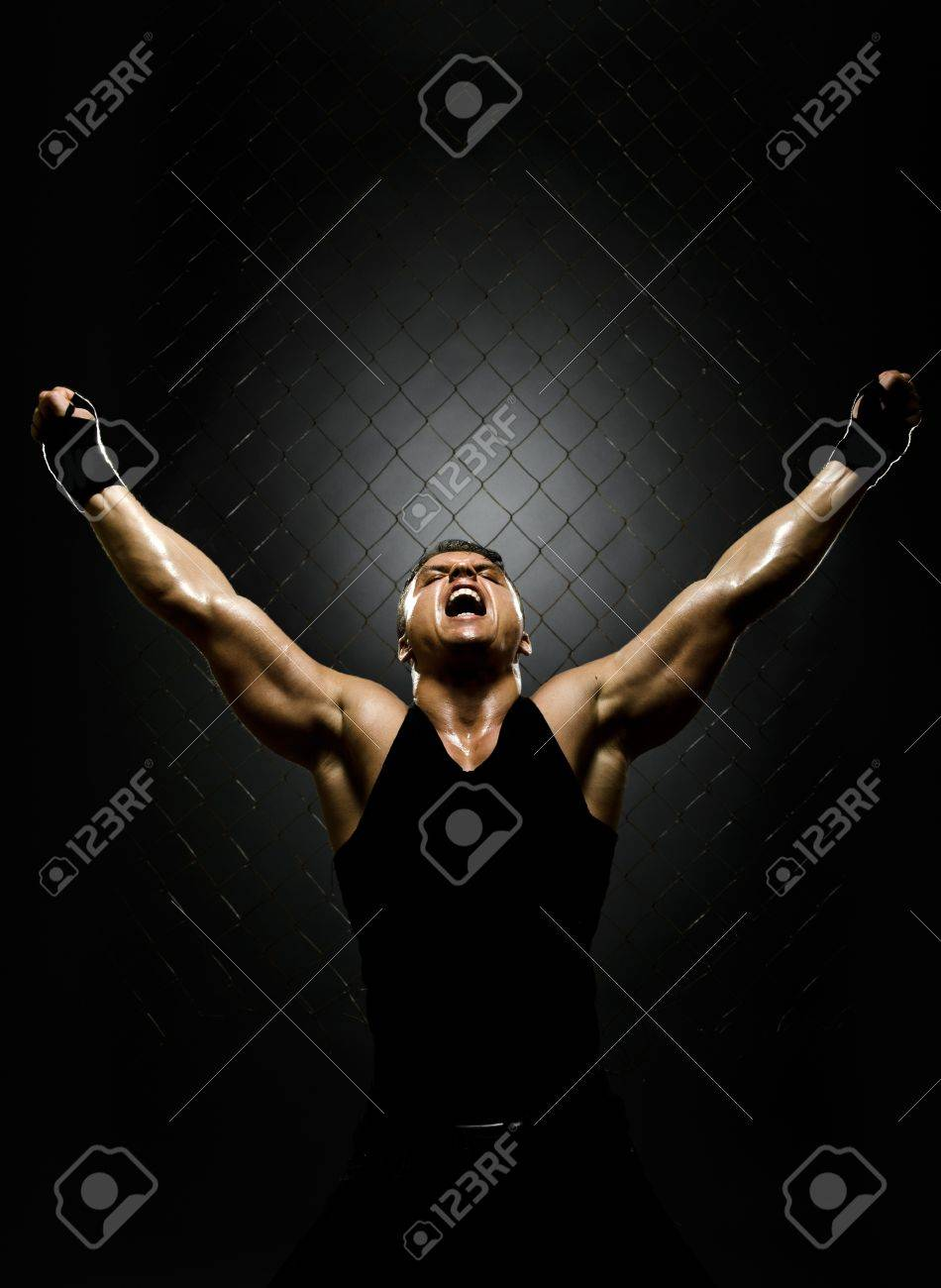 vertrical photo  muscular young  guy street-fighter,  triumphant cries  yell , hard light Stock Photo - 15165287