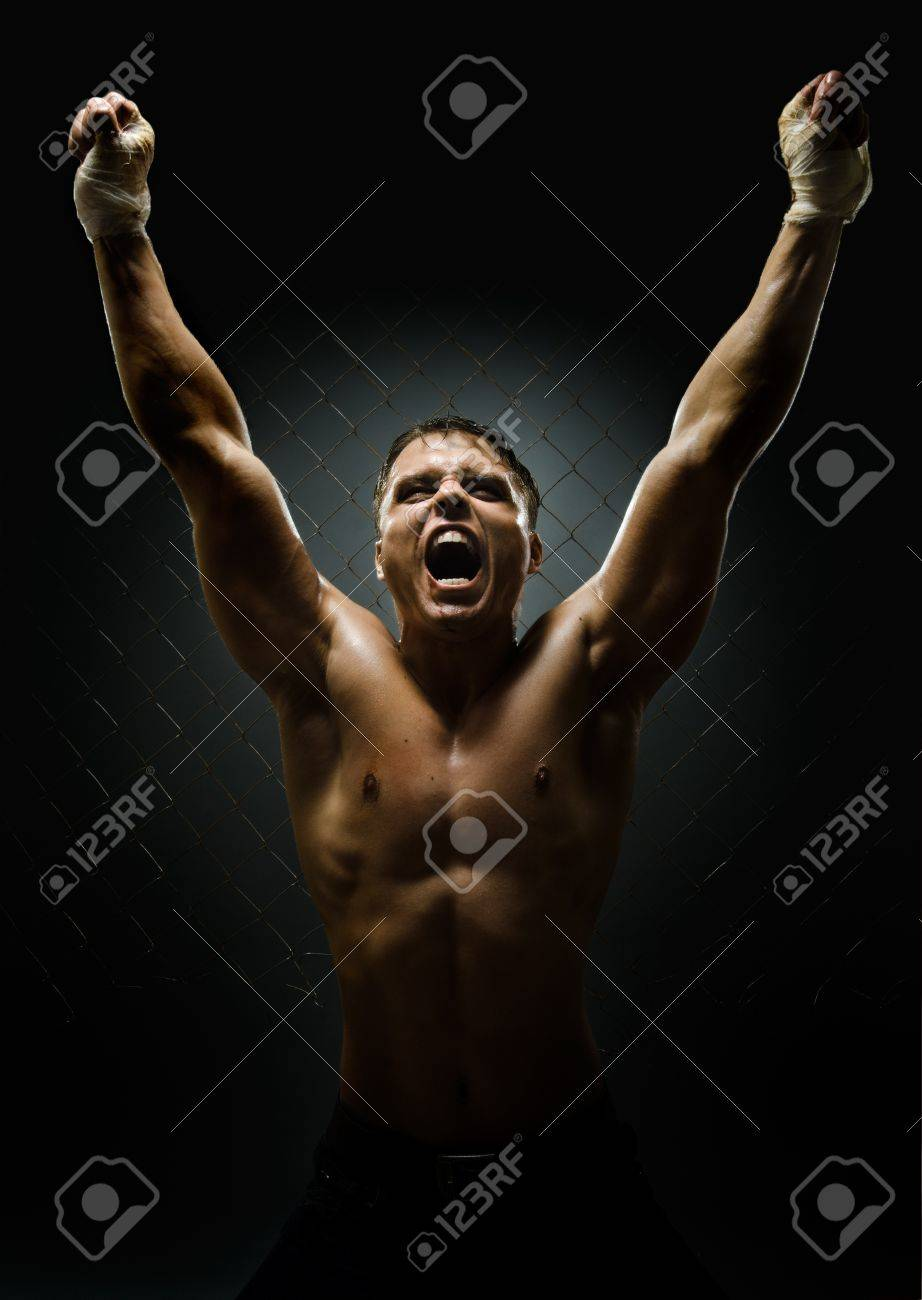 vertrical photo  muscular young  guy street-fighter,  triumphant cries  yell , hard light Stock Photo - 15497170