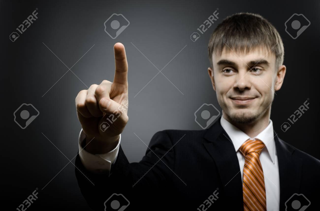 handsome businessman  finger point touch, on dark grey background Stock Photo - 15497173