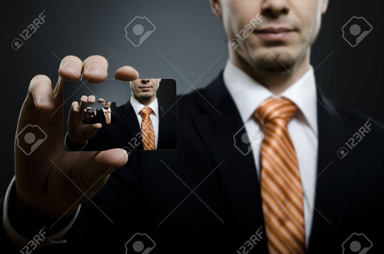 businessman in black costume and orange necktie reach out on camera and show credit card , close up Stock Photo - 15832569