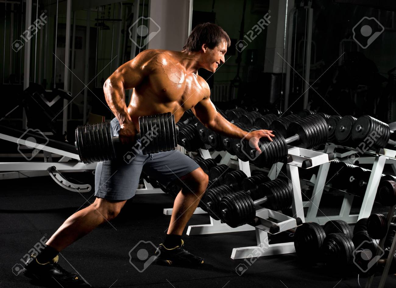 very power athletic guy ,  execute  traction with  dumbbells, exercise on broadest muscle of back, in sport hall Stock Photo - 17646431