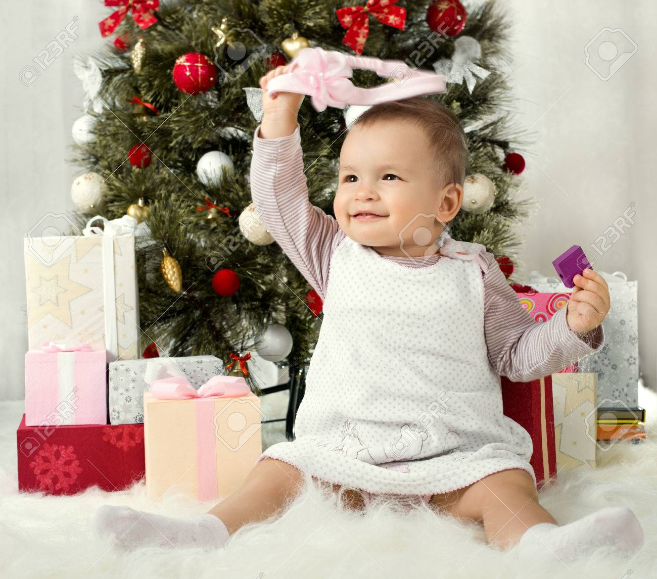 one-year-old little girl solemnize Christmas, sit under Christmas-tree with gift Stock Photo - 23758434