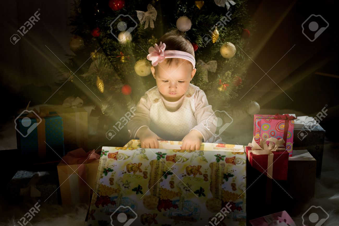 one-year-old little girl solemnize Christmas, sit under Christmas-tree and reach gift of box, horizontal photo Stock Photo - 23867997