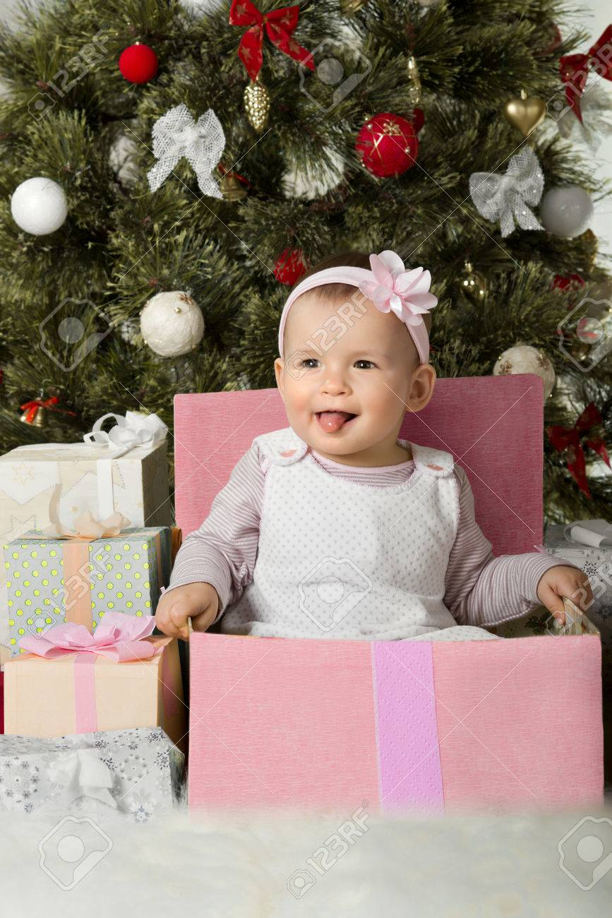 one-year-old little girl solemnize Christmas, sit under Christmas-tree with gift, vertical photo Stock Photo - 23758436