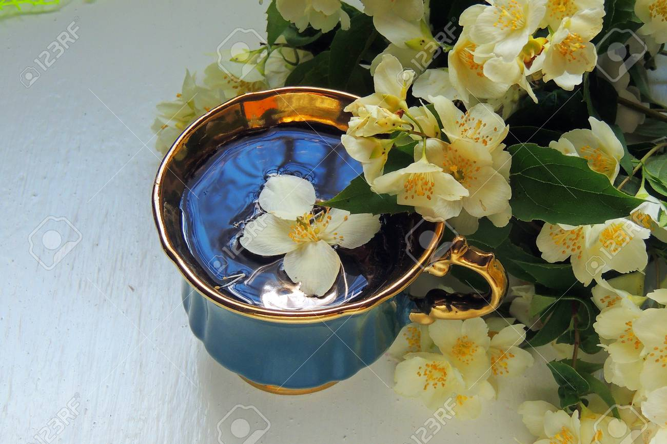 Jasmine Flowers And Cup Of Tea On Rustic Background Top View Stock