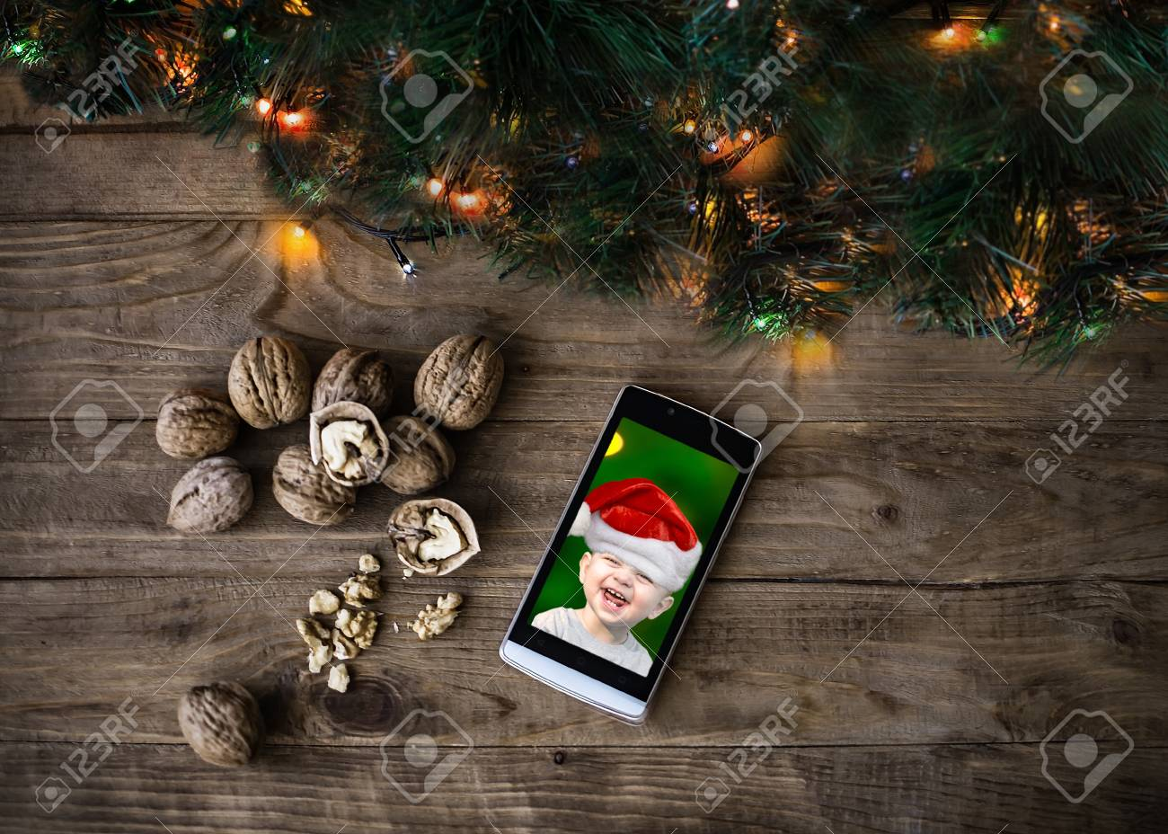 648c174975da1 ... lights on wooden background. Christmas and New Year card with copy  space. Mobil phone with a laughing baby in a red Santa Claus hat