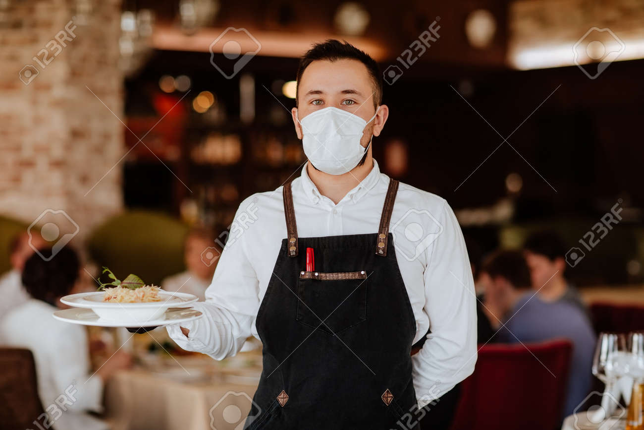 Young handsome waiter in black apron and medical mask holding plate with spaghetti against restaurant background. - 167651307
