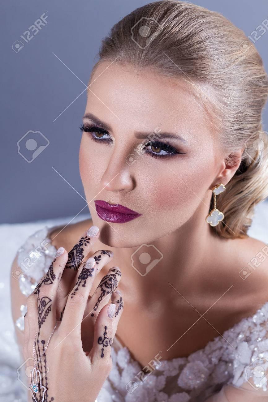 Mariée Blonde élégante Avec Maquillage Fort Et Coiffure De Mariage Sur Fond Bleu